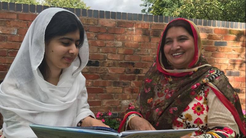 In this picture, Malala Yousafzai is sitting with her mother Toor Pekai reading her new book Malala's Magic Pencil. (Photo: Twitter / Malala Yousafza)