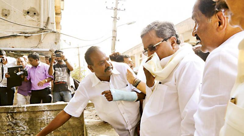 Chief Minister Siddaramaiah covers his nose during an inspection of rain-affected areas in Bengaluru on Wednesday(Photo:DC)