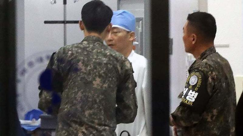 South Korean military officers, wearing armbands of the Joint Security Area of Panmunjom, talk with a doctor at a hospital in Suwon, south of Seoul. (Photo: AFP)