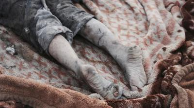 A body lies in a blanket at the site of a mass grave containing some two dozen people, many of them children, in an area recently re-taken from Islamic State militants in Mosul, Iraq.