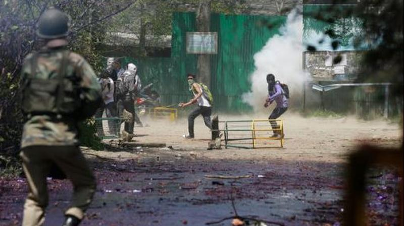 Kashmiri students throw stones on Indian policemen as tear smoke shell explodes near them. (Photo: PTI)