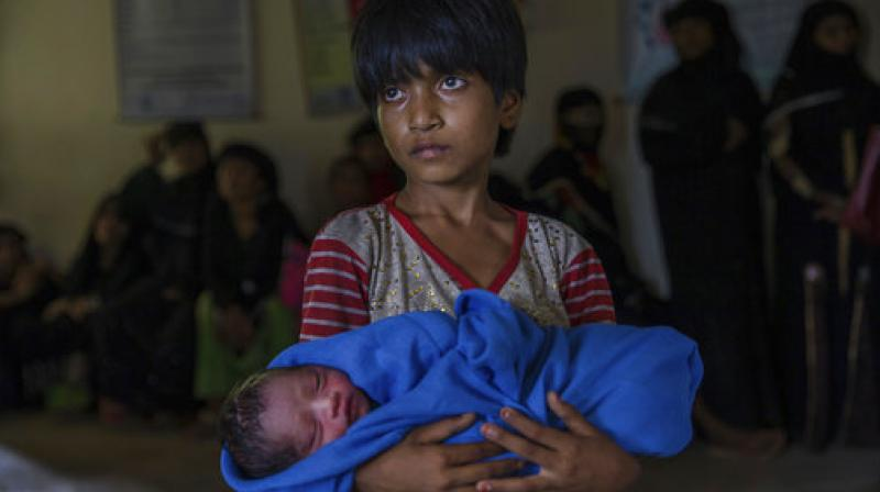 Rohingya Muslim girl Afeefa Bebi, who recently crossed over from Myanmar into Bangladesh, holds her few-hours-old brother as doctors check her mother Yasmeen Ara at a community hospital in Kutupalong refugee camp. (Photo: PTI)