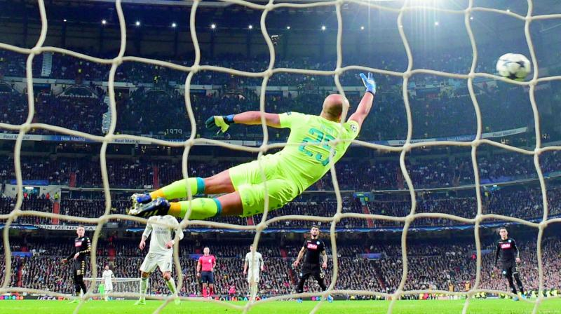 Napoli's goalkeeper from Spain Pepe Reina dives for the ball as Real Madrid's Brazilian midfielder Casemiro scores a goal during the UEFA Champions League Round of 16 first leg football match at the Santiago Bernabeu stadium in Madrid. Real won 3-1. (Photo: AFP)