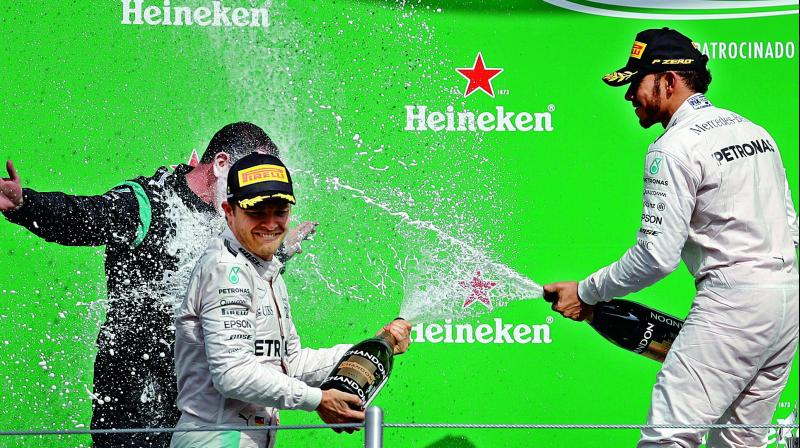Mercedes' Lewis Hamilton (right) celebrates with team mate Nico Rosberg after winning the Mexico GP at the Hermanos Rodriguez racetrack on Sunday. Hamilton finished ahead of Rosberg and Ferrari's Sebastian Vettel. (Photo: AP)