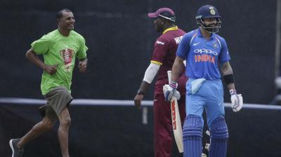 India's captain Virat Kohli, right, leaves the field as rain delays the first ODI cricket match against West Indies at Queen's Park Oval in Port of Spain (Photo: AP)
