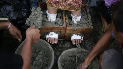 Dozens of farmers and activists opposed to the cement factory have encased their feet in concrete during a days-long protest in Jakarta.