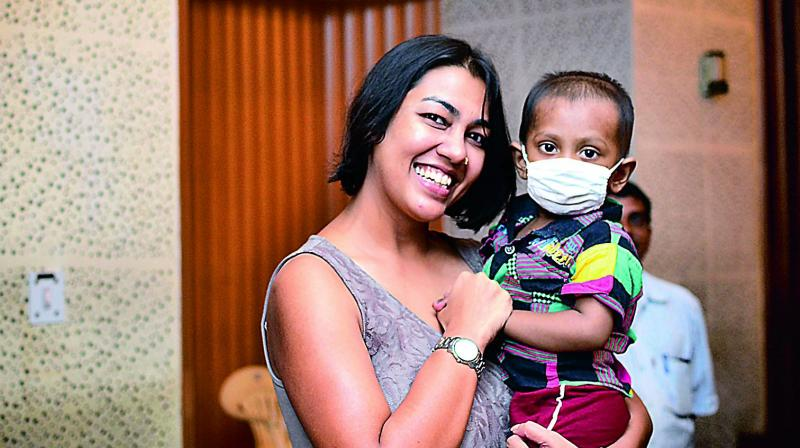 Happy to help: Purnota poses with one of the children associated with the foundation