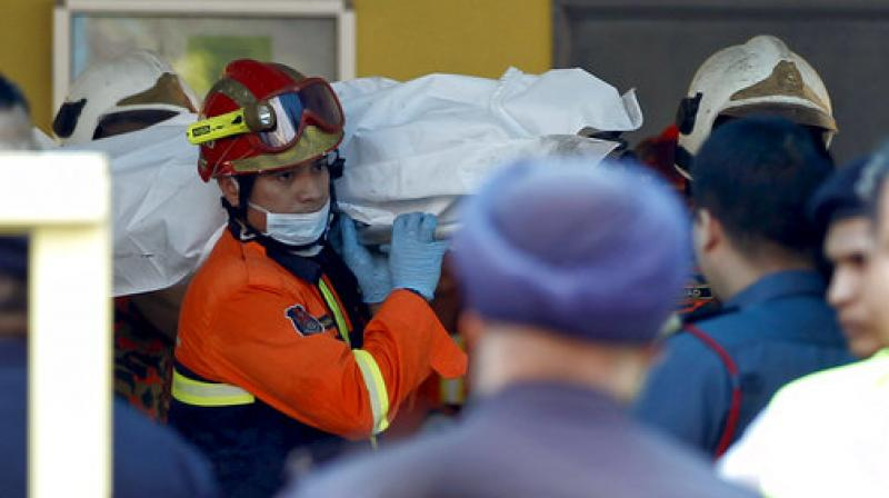 The body of a victim is carried out by rescue personnel from an Islamic religious school after a fire on the outskirts of Kuala Lumpur (Photo: AP)
