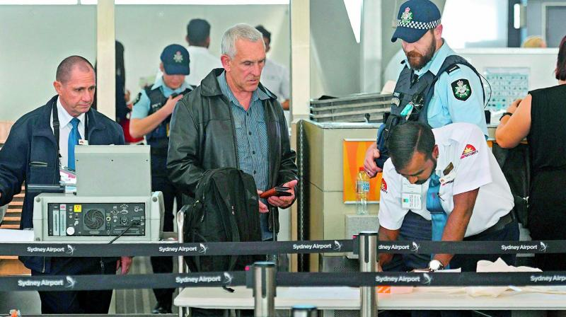 Police help screen passengers at Sydney Airport on Sunday. (Photo: AFP)