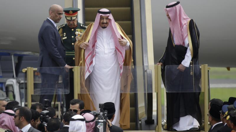 Saudi King Salman adjusts his headscarf as he steps down the stairs of his plane upon arrival at Halim Perdanakusuma Airport in Jakarta