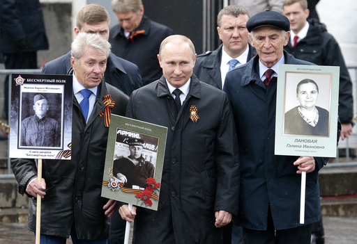 Russian President Vladimir Putin was present with a photograph of his father in a naval uniform. He stood with people carrying portraits of relatives who fought in World War II, during the Immortal Regiment march in Red Square, in Moscow, Russia, Tuesday May 9, 2017. (Photo: AP)