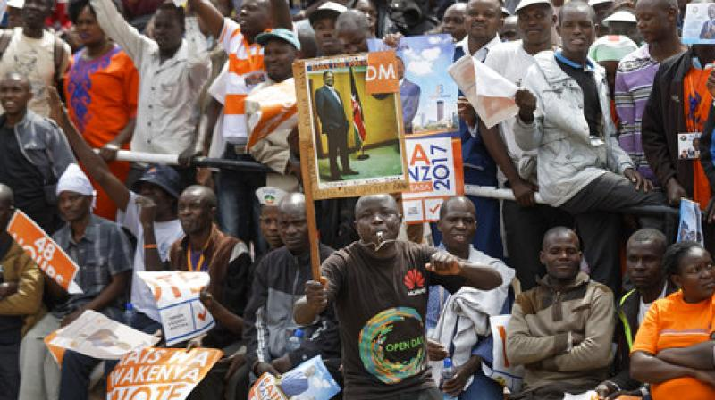 A supporter holds up a placard of opposition leader Raila Odinga at his final electoral campaign rally in Uhuru Park in downtown Nairobi, Kenya. (Photo: File/AP)