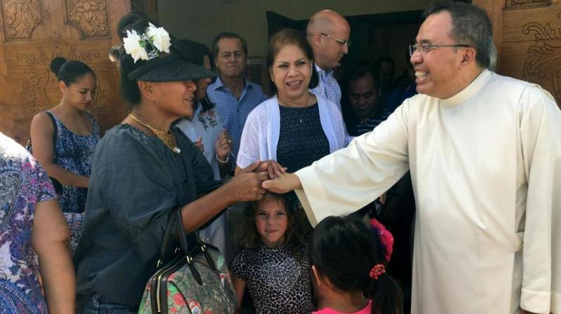 "Pastor Fr. Jose Antonio"" Lito"" P. Abad, right, greets parishioners as they leave Blessed Diego de San Vitores Church following Sunday Mass in Tumon, Guam. (Photo: AP)"