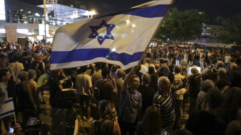 Israelis take part in a weekly protest against Israeli Prime Minister Benjamin Netanyahu, seen on the poster, in front of the home of Israel's attorney general Avichai Mandelblit in Petah Tikva. (Photo: AP)