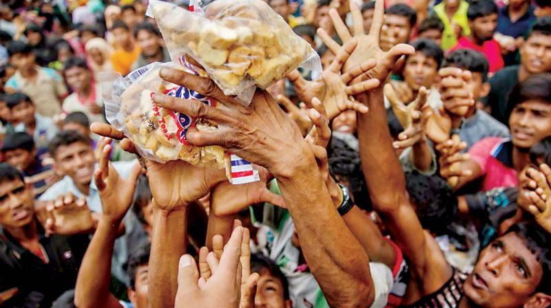 Rohingya Muslims, who crossed over from Myanmar into Bangladesh, stretch their arms out to receive packets of biscuits thrown at them as handouts. (Photo: AP)