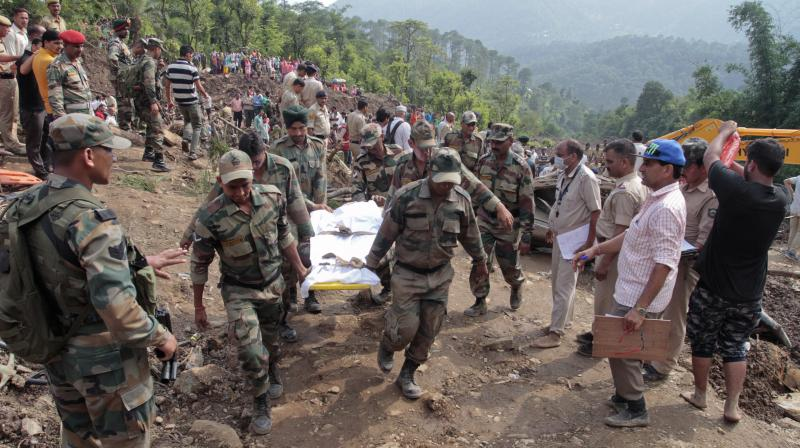 Army soldiers and rescue workers recover bodies of landslide victims even as they try to pull out two buses that were covered in mud after a landslide triggered by heavy monsoon rain in Urla village Himachal Pradesh