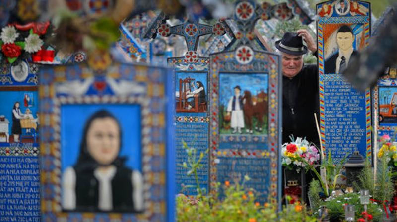 A man cries at a relative's grave standing between the painted crosses in the Merry Cemetery, in Sapanta, northwestern Romania, Sunday, Sept. 10, 2017. (Photo: AP)