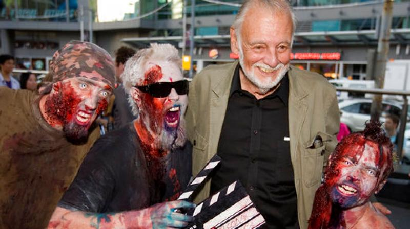 In this, Sept. 12, 2009, file photo, director George Romero poses with some fans dressed as zombies after accepting a special award during the Toronto International Film Festival in Toronto. (Photo: AP)