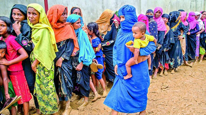 Newly arrived Rohingya women wait for their turn to collect building material for their shelters distributed by aid agencies in Kutupalong refugee camp