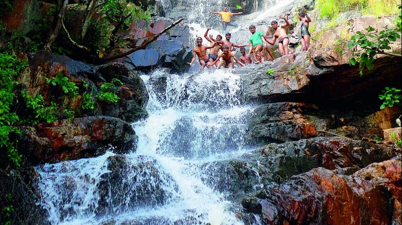 Villagers enjoy themselves at the naturally-formed waterfall located in the Saidapur forest area (Photo: DC)