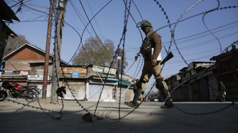 An Indian paramilitary soldier guards at a check point during a strike in Srinagar Kashmir