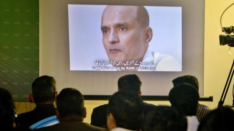 Journalists look at an image of former Indian naval officer Kulbhushan Jadhav. (Photo: AP)