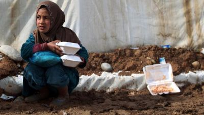 An Iraqi girl, displaced from Mosul, carries food rations as she sits near a tent at the Hammam al-Alil camp for the internally displaced, south of Mosul.