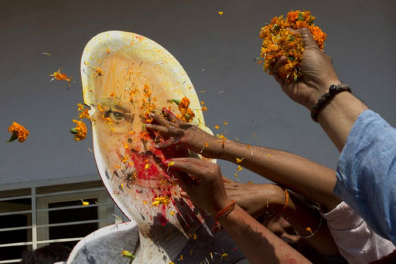 BJP supporters toss flowers on the cutout of Indian Prime Minister Narendra Modi as they celebrate winning seats in the state of Uttar Pradesh in Lucknow.
