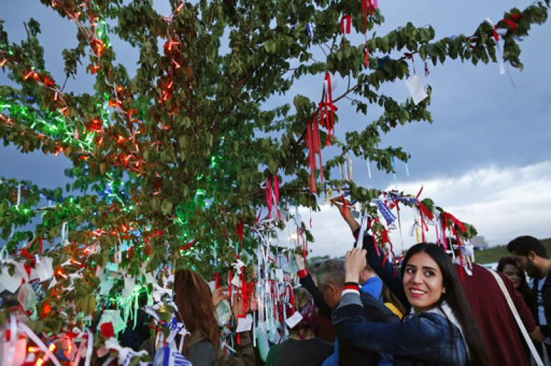 A woman poses for photographs by a tree, decorated with ribbons and wishes during celebrations for the 'Hidirellez' festival. (Photo: AP)