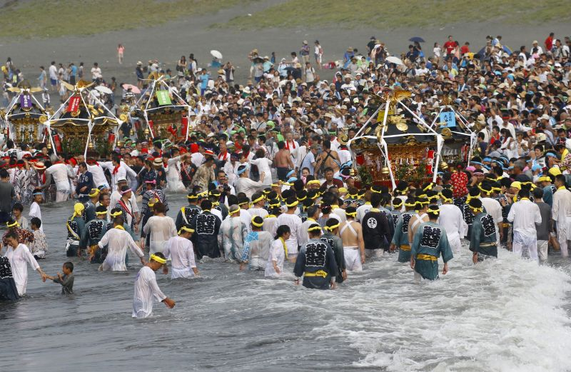 Participants cheer on a portable shrine carried by others as they parade through the sea during a purification rite at the annual Hamaori Festival at Southern beach in Chigasaki, west of Tokyo Monday, July 17, 2017. (AP Photo/Shizuo Kambayashi)