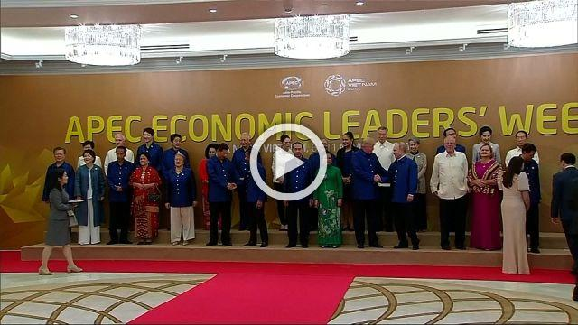 Trump, Putin shake hands during APEC family photo